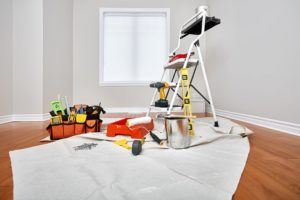 Painting tools and ladder in a room getting ready for painting services